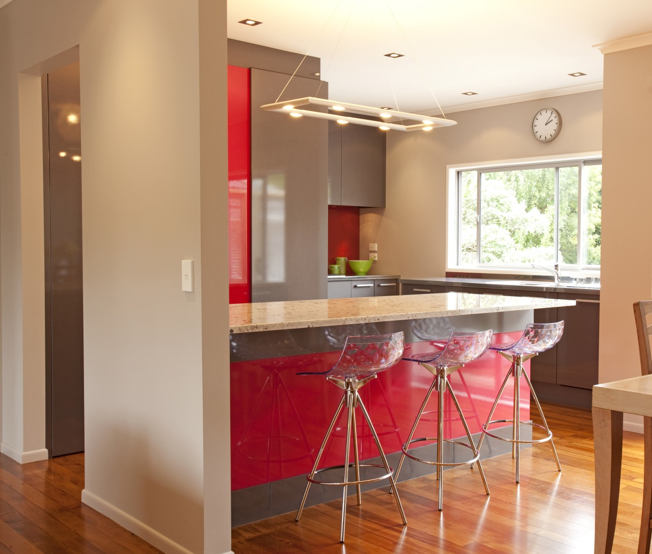 Streamlined grey kitchen with red accents. Wooden floors, cabinetry, ceiling, countertop, dining room, floor, flooring, hardwood, home, interior design, kitchen, property, real estate, room, table, wood flooring, orange, brown