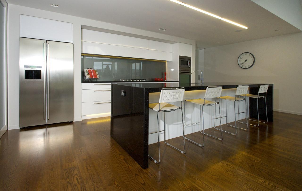 This modern kitchen is by Kitchen Focus. The countertop, floor, flooring, hardwood, interior design, kitchen, laminate flooring, real estate, room, wood flooring, brown, gray