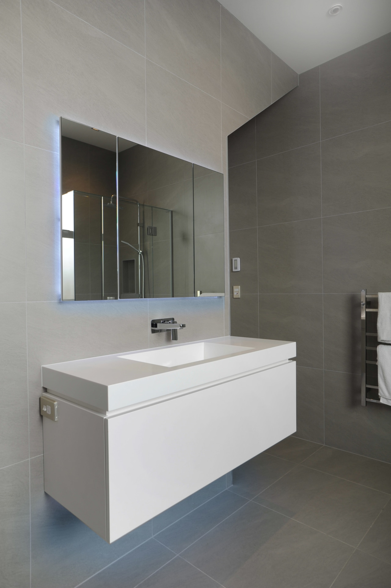 Monochromatic and dramatic, this bathroom is brought together architecture, bathroom, bathroom accessory, bathroom cabinet, floor, interior design, product design, room, sink, tap, tile, wall, gray