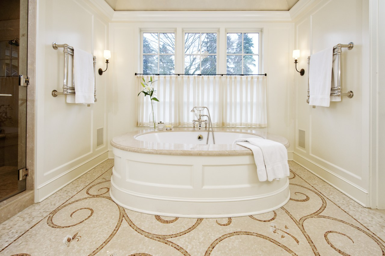 A large round tub with a marble surround bathroom, bathtub, estate, floor, flooring, home, interior design, plumbing fixture, property, real estate, room, tile, wall, window, wood flooring, white