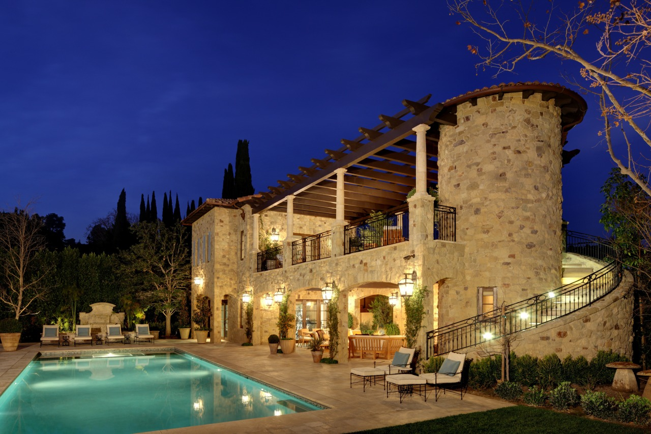 The rustic guest house includes a balcony, covered architecture, building, estate, evening, hacienda, home, hotel, house, landscape lighting, lighting, mansion, night, property, real estate, reflection, sky, villa, blue, brown