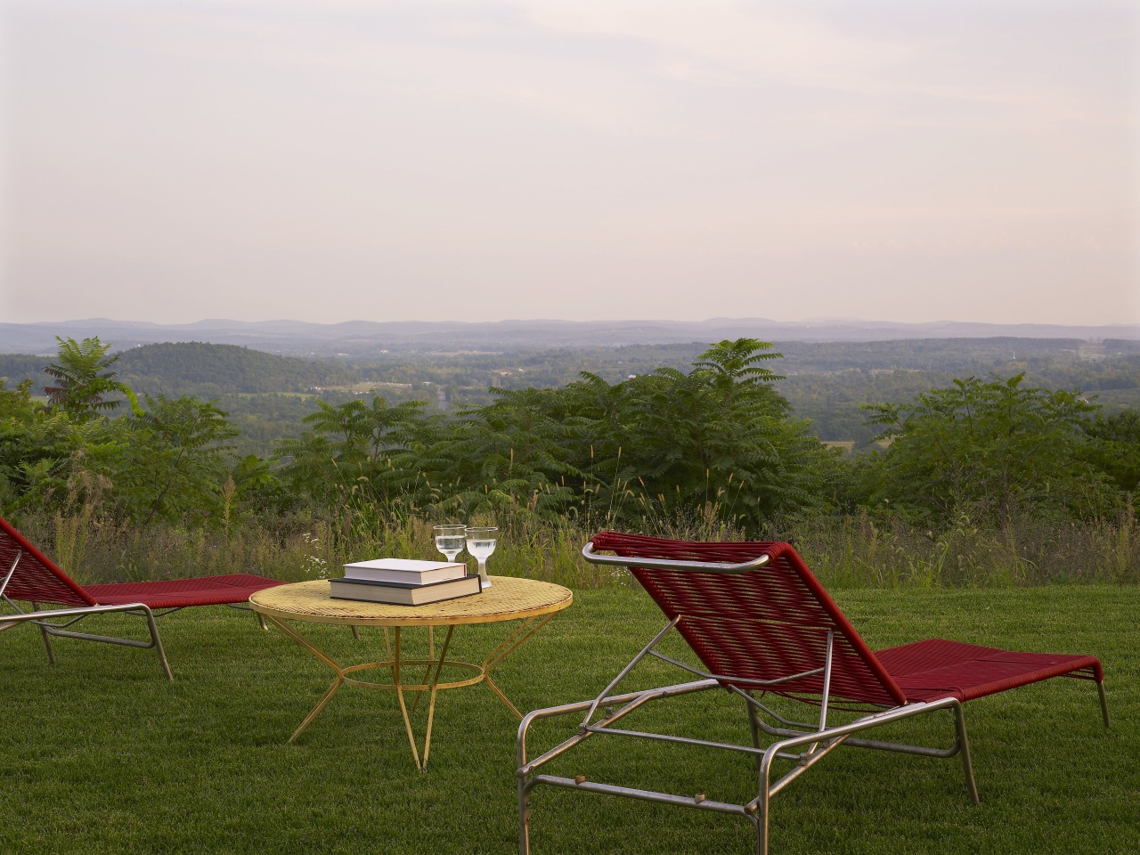 Sitting high on a natural plateau, this house chair, field, furniture, grass, grassland, house, landscape, leisure, meadow, outdoor furniture, plain, plant, rural area, sky, sunlounger, table, tree, brown, white