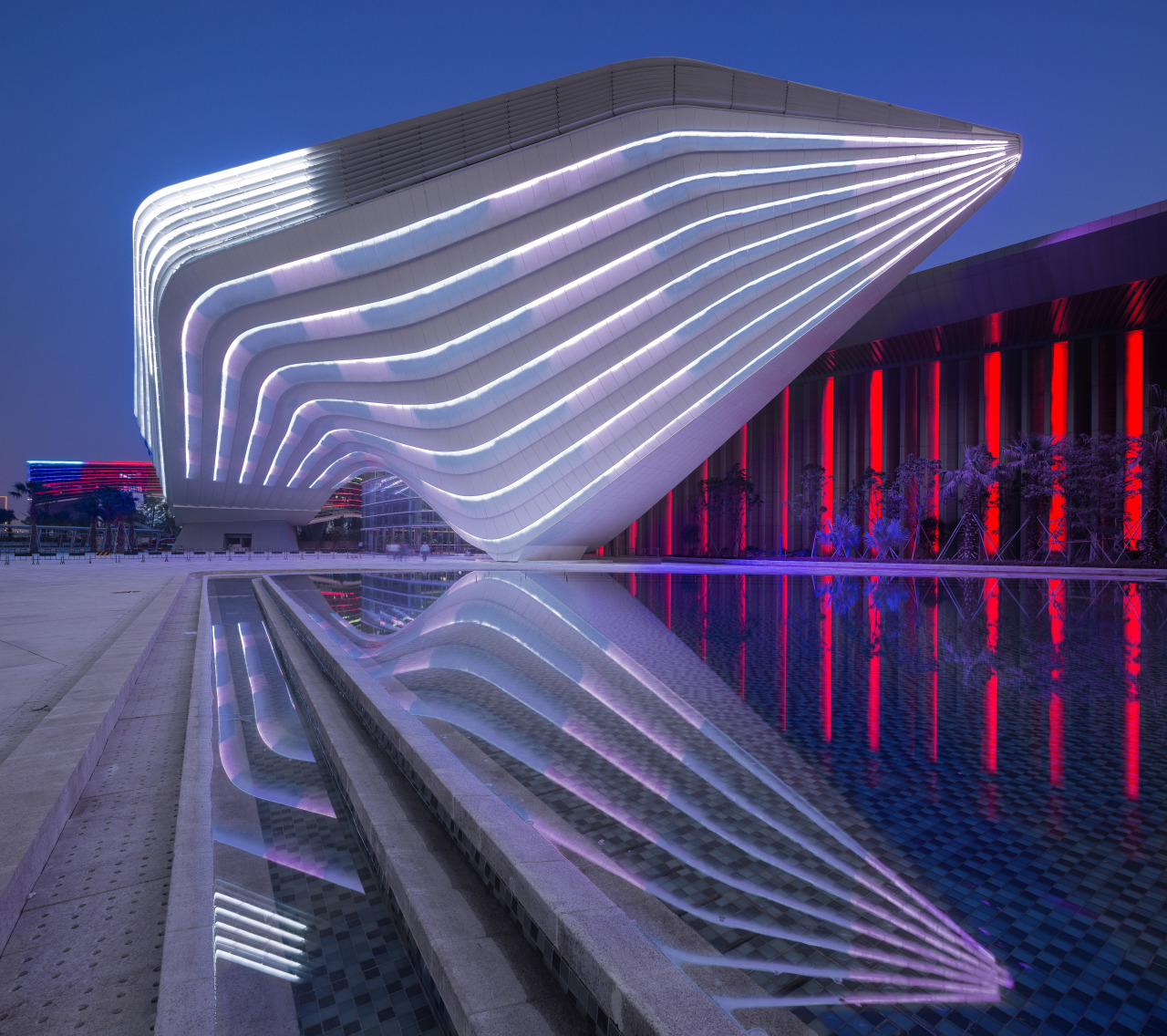 An architectural ribbon winds around the Zhuhai International architecture, building, corporate headquarters, daylighting, facade, landmark, light, lighting, line, metropolis, metropolitan area, purple, reflection, sky, skyscraper, structure, blue, purple