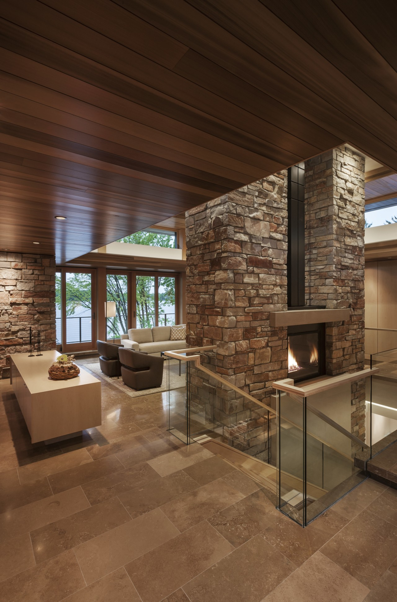 The warm palette of natural materials in this architecture, ceiling, fireplace, floor, flooring, home, interior design, living room, lobby, real estate, wood, wood flooring, brown