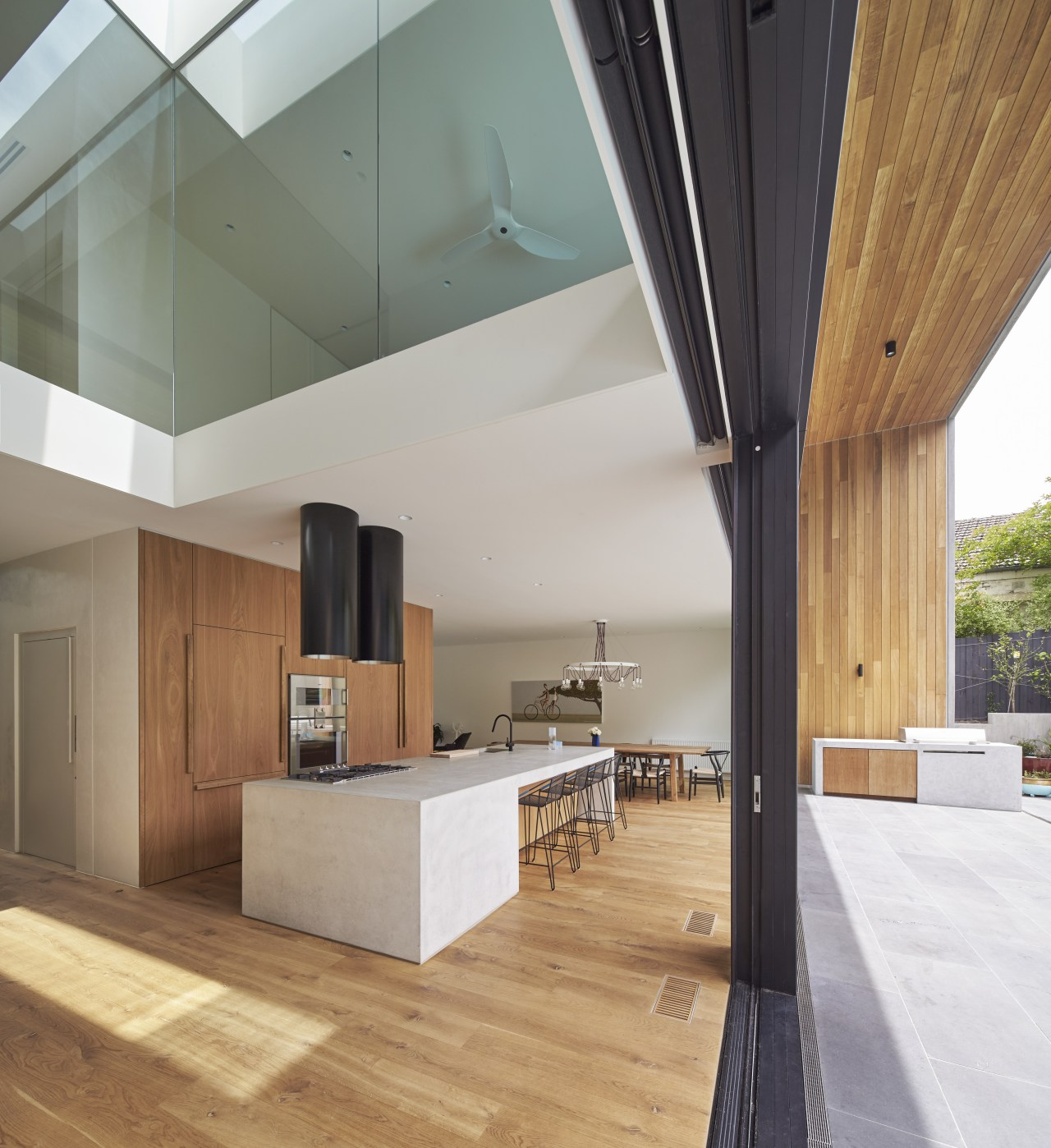 The rear facade is fully operable, with glazed architecture, ceiling, daylighting, floor, flooring, hardwood, house, interior design, laminate flooring, loft, real estate, wood, wood flooring, gray