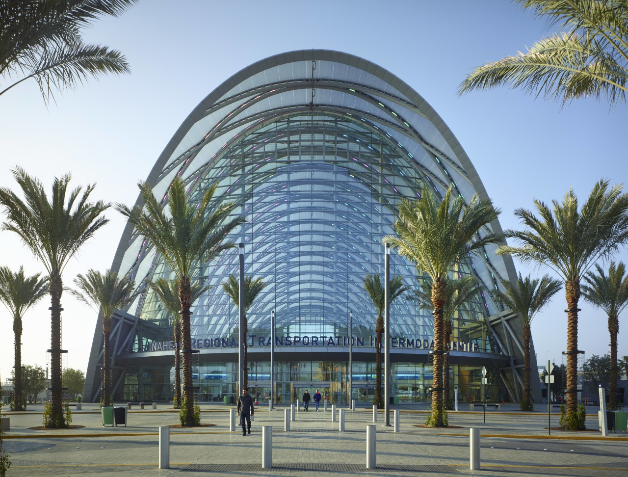 The new ARTIC transit hub in Anaheim is architecture, arecales, building, city, condominium, corporate headquarters, hotel, metropolitan area, mixed use, palm tree, plant, sky, tree, teal