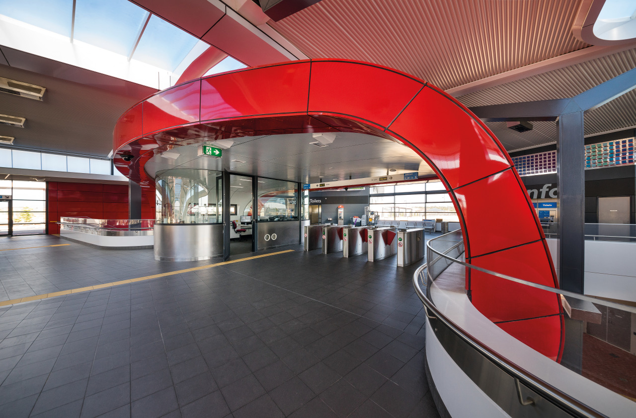A curved, bright red interior canopy frames the airport terminal, architecture, metropolitan area, public transport, structure, transport, red, gray
