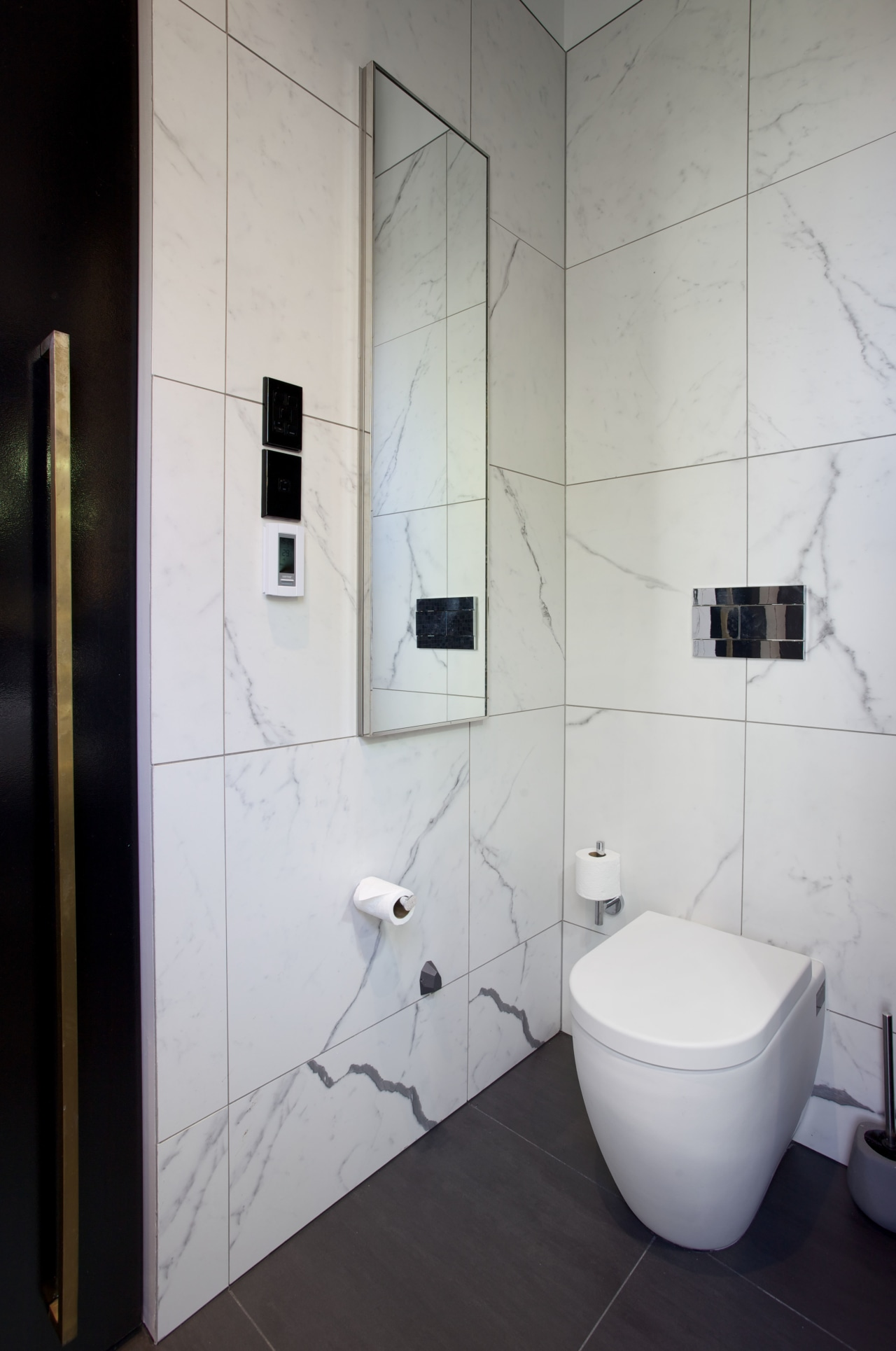 Black, white and touches of brass all come bathroom, floor, interior design, plumbing fixture, product design, public toilet, room, tile, toilet, wall, gray