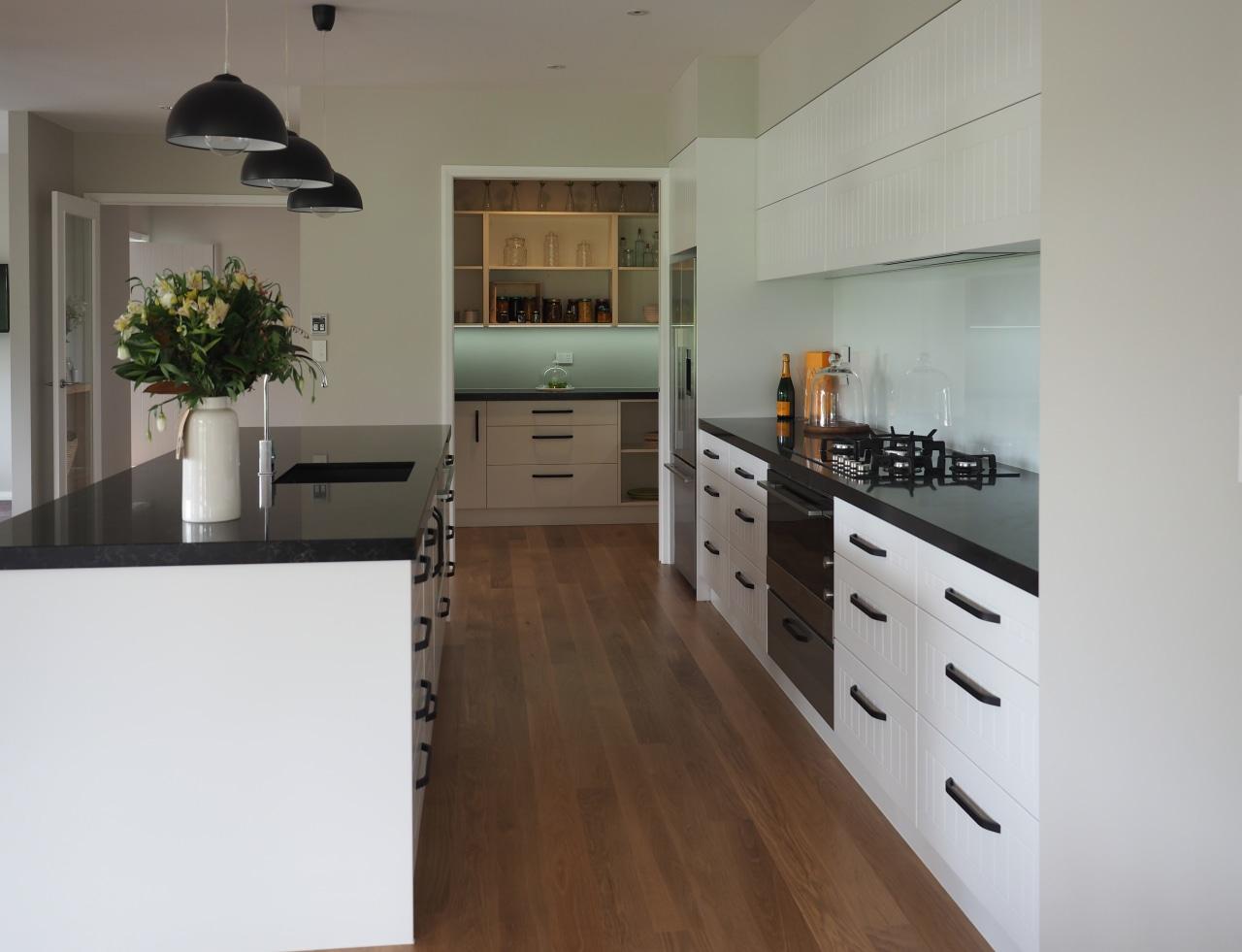 This modern kitchen in Landmark show home has cabinetry, countertop, cuisine classique, floor, flooring, hardwood, interior design, kitchen, room, wood flooring, gray