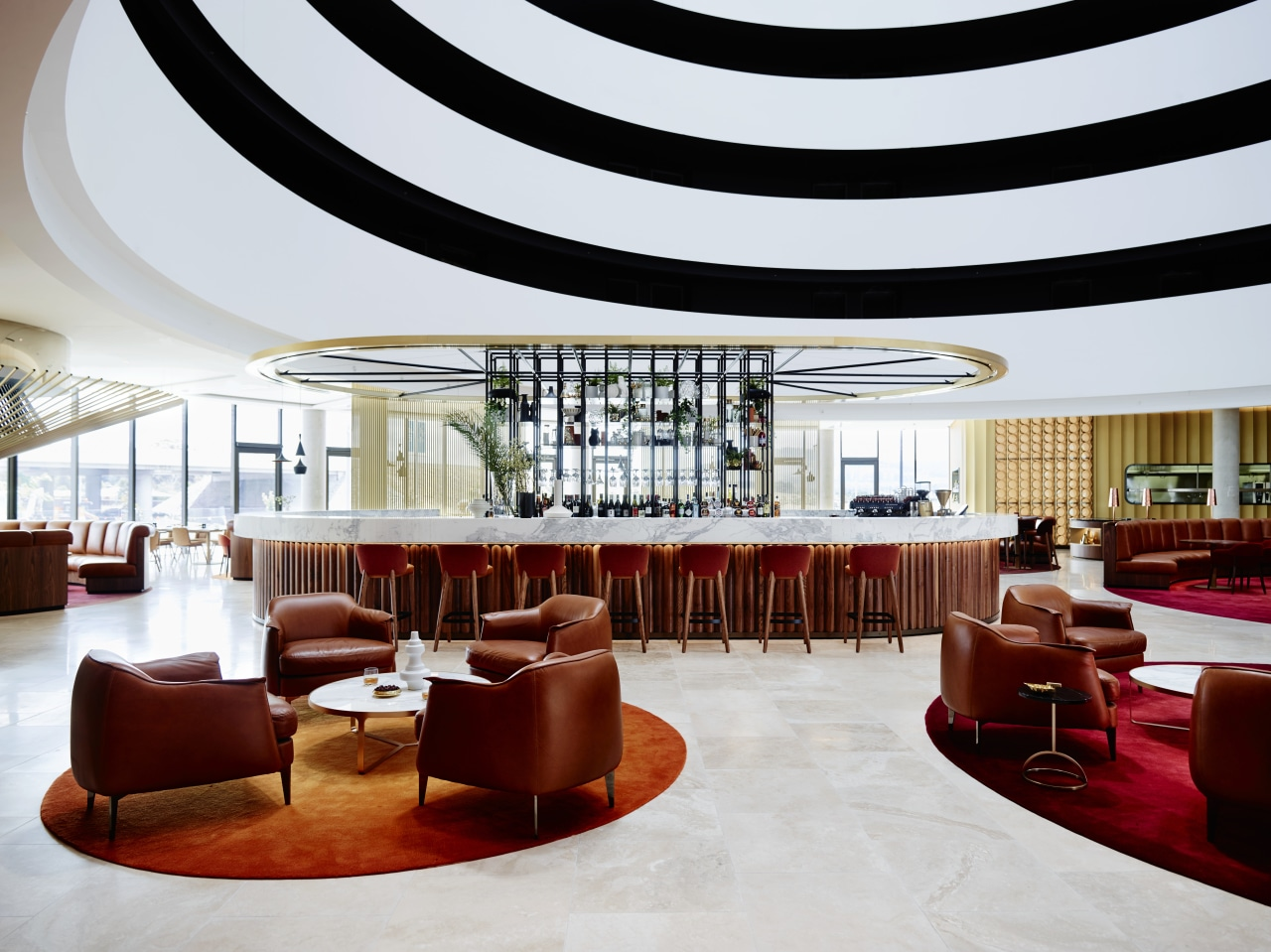 A curvaceous bar area provides the social focal ceiling, function hall, interior design, lobby, restaurant, table, white