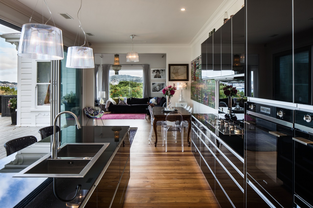 The black glass kitchen surfaces complement the transparent countertop, interior design, kitchen, real estate, black, gray