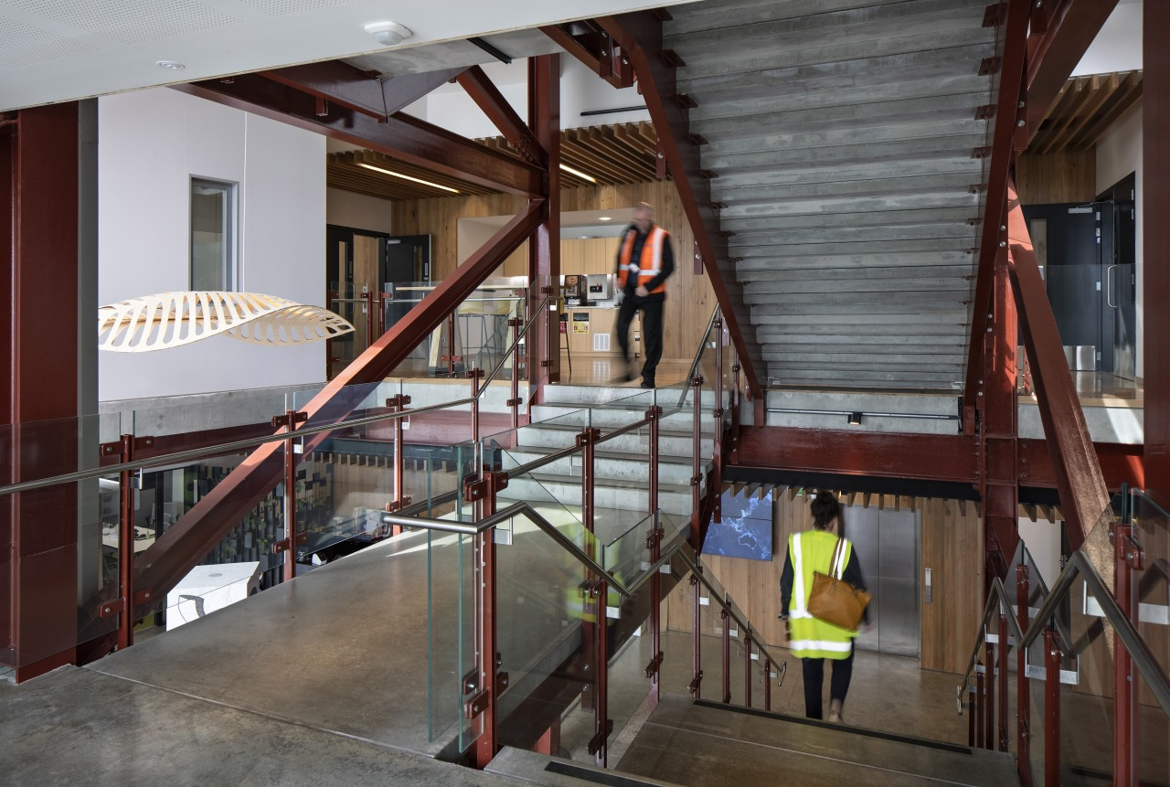 The interior palette at Lyttleton Port's Waterfront House architecture, beam, building, ceiling, daylighting, floor, handrail, ladder, lobby, loft, room, stairs, gray, red