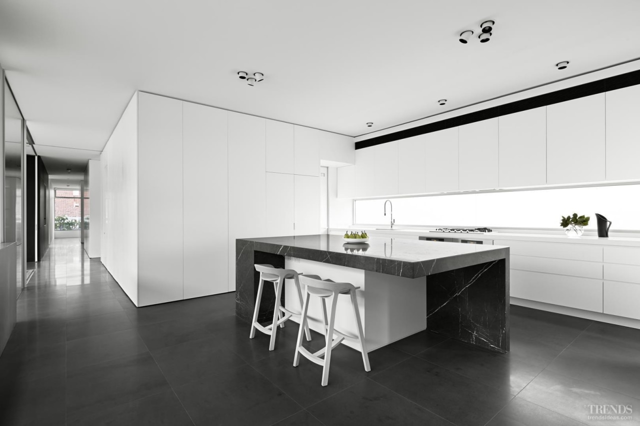 Positioned between the two living areas, the kitchen architecture, black and white, countertop, floor, house, interior design, kitchen, real estate, white, black
