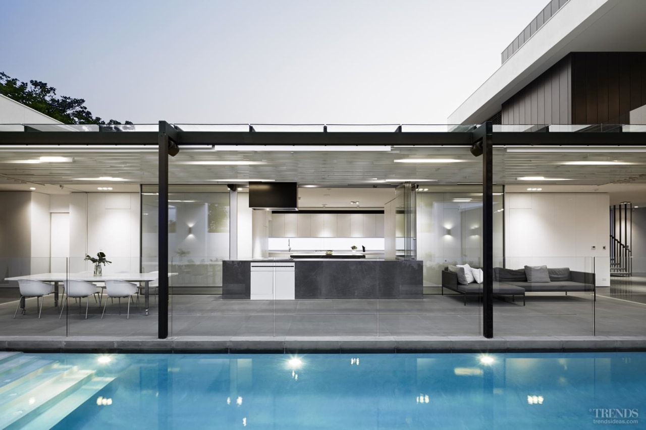 There is a long serving counter facing the architecture, condominium, home, house, interior design, property, real estate, swimming pool, white, gray
