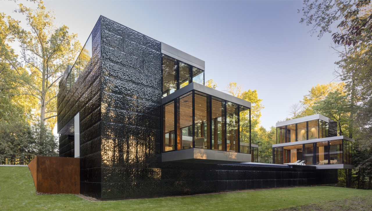 Crisp glazed volumes pop from the house's rough-hewn