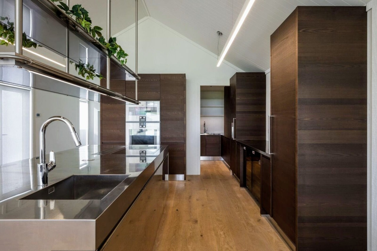 The open plan has a good flow to architecture, cabinetry, countertop, floor, flooring, hardwood, house, interior design, kitchen, real estate, wood, wood flooring, black, gray
