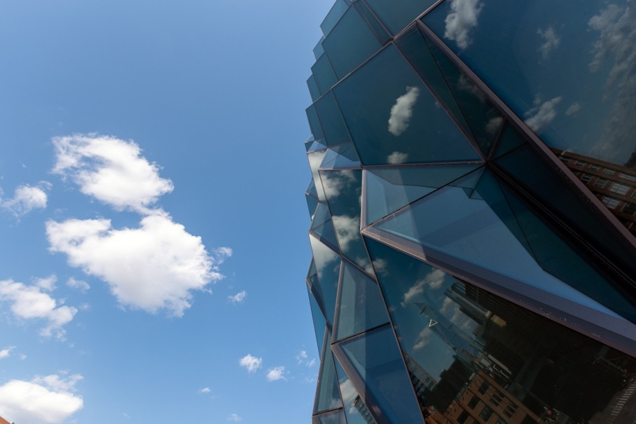 The facade features high-performance glass with low reflectivity. architecture, blue, city, cloud, daytime, glass, photography, reflection, sky, sunlight, urban area, teal, blue
