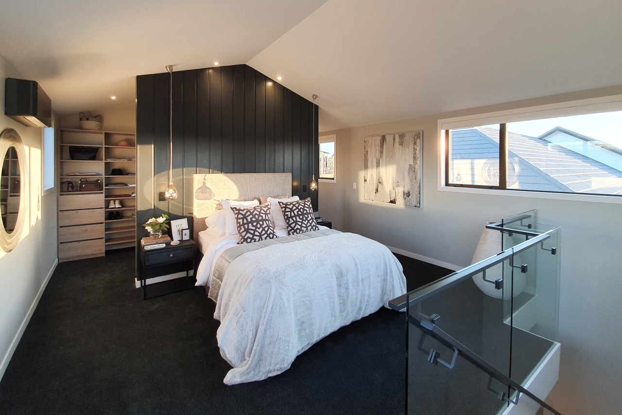 A floor-to-ceiling bedhead separates bedroom from dressing area.