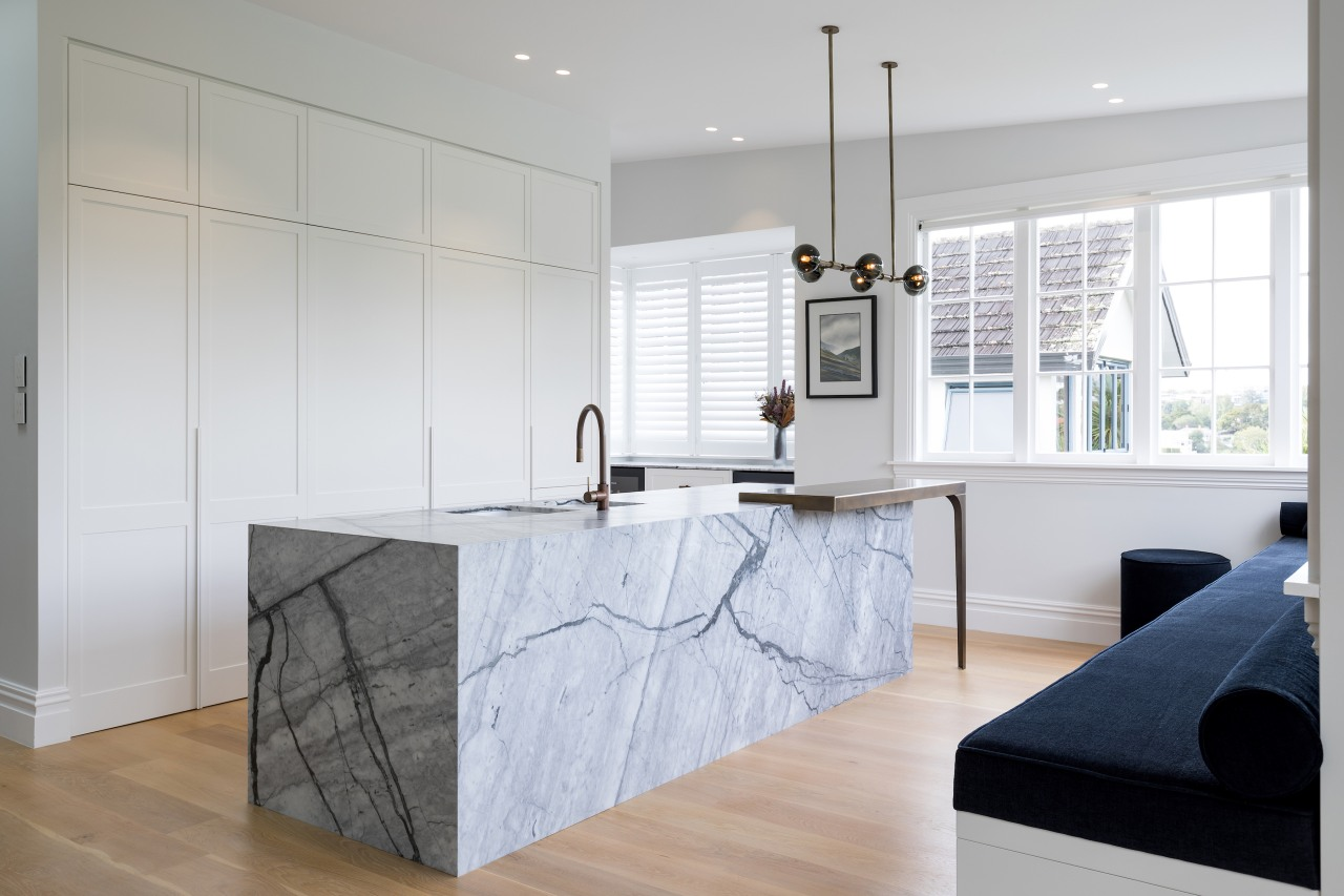 A handle-less floor-to-ceiling wall of white cabinetry provides