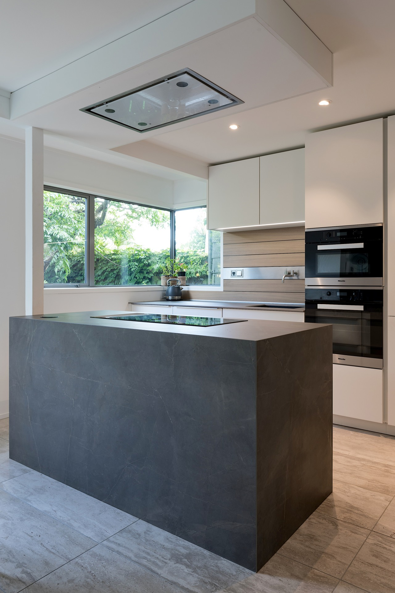 The bulkhead with extractor echoes the proportions of architecture, building, cabinetry, ceiling, concrete, countertop, design, floor, flooring, furniture, home, house, interior design, kitchen, kitchen stove, material property, plywood, property, real estate, room, table, tile, gray