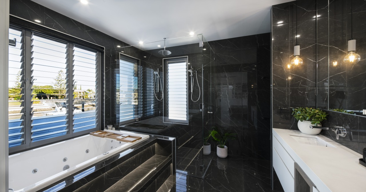 The bath in this luxurious bathroom features recessed architecture, bathroom, building, ceiling, estate, floor, furniture, home, house, interior design, property, real estate, room, tile, black
