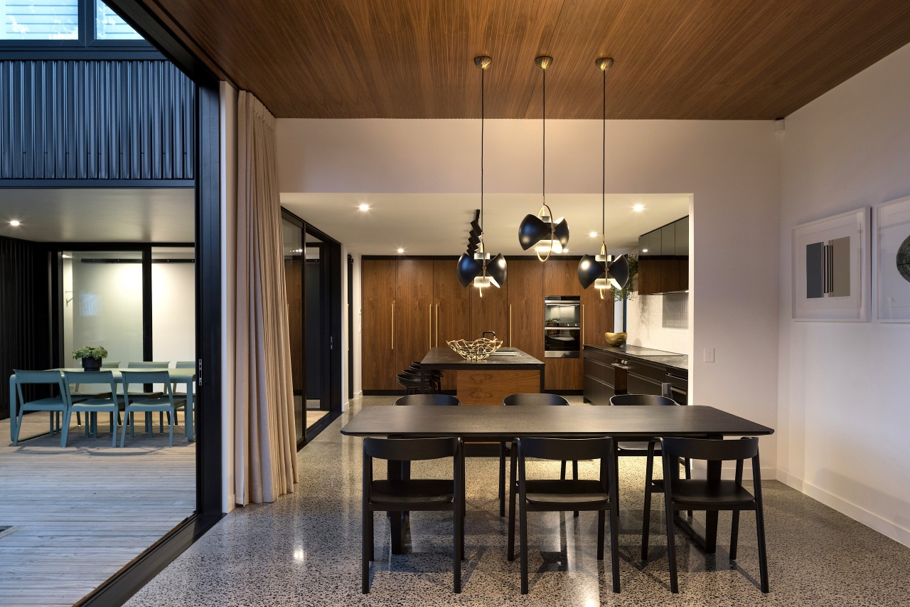 This black and wood kitchen connects with the