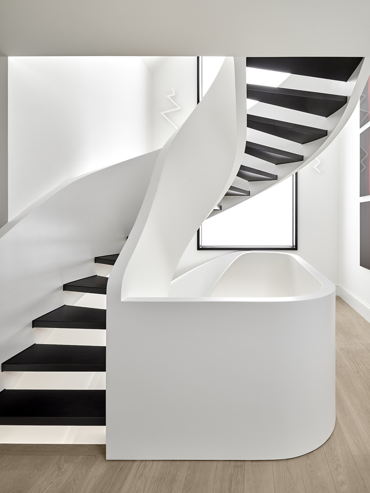 In two sweeping runs, this sculptural staircase knits white