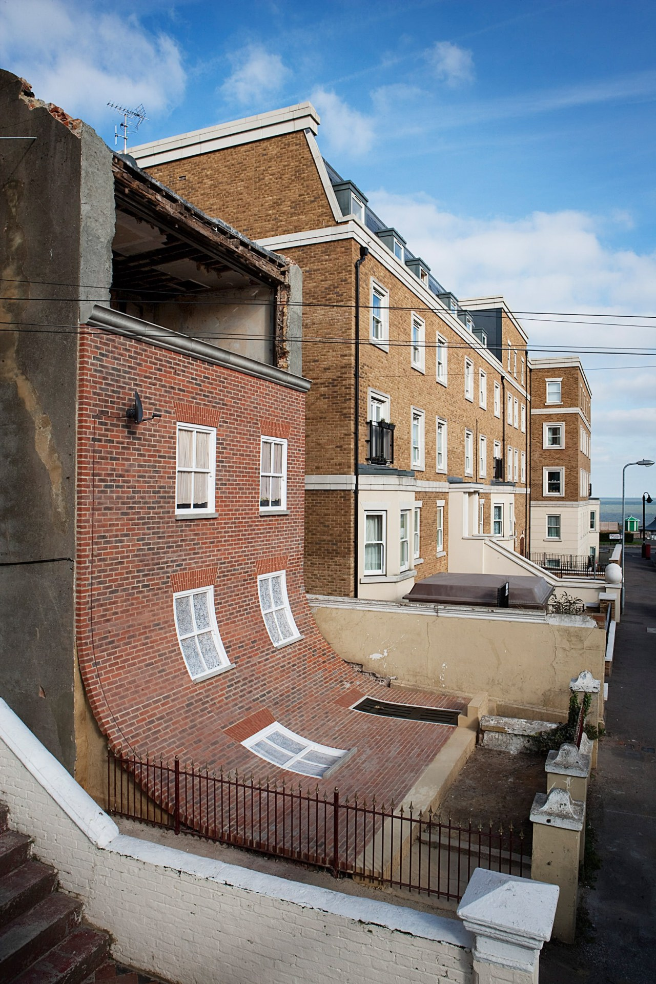 Alex Chinneck – From the knees of my apartment, architecture, blue, brick, brickwork, building, facade, home, house, neighbourhood, property, real estate, residential area, roof, street, town, urban area, wall, window, gray