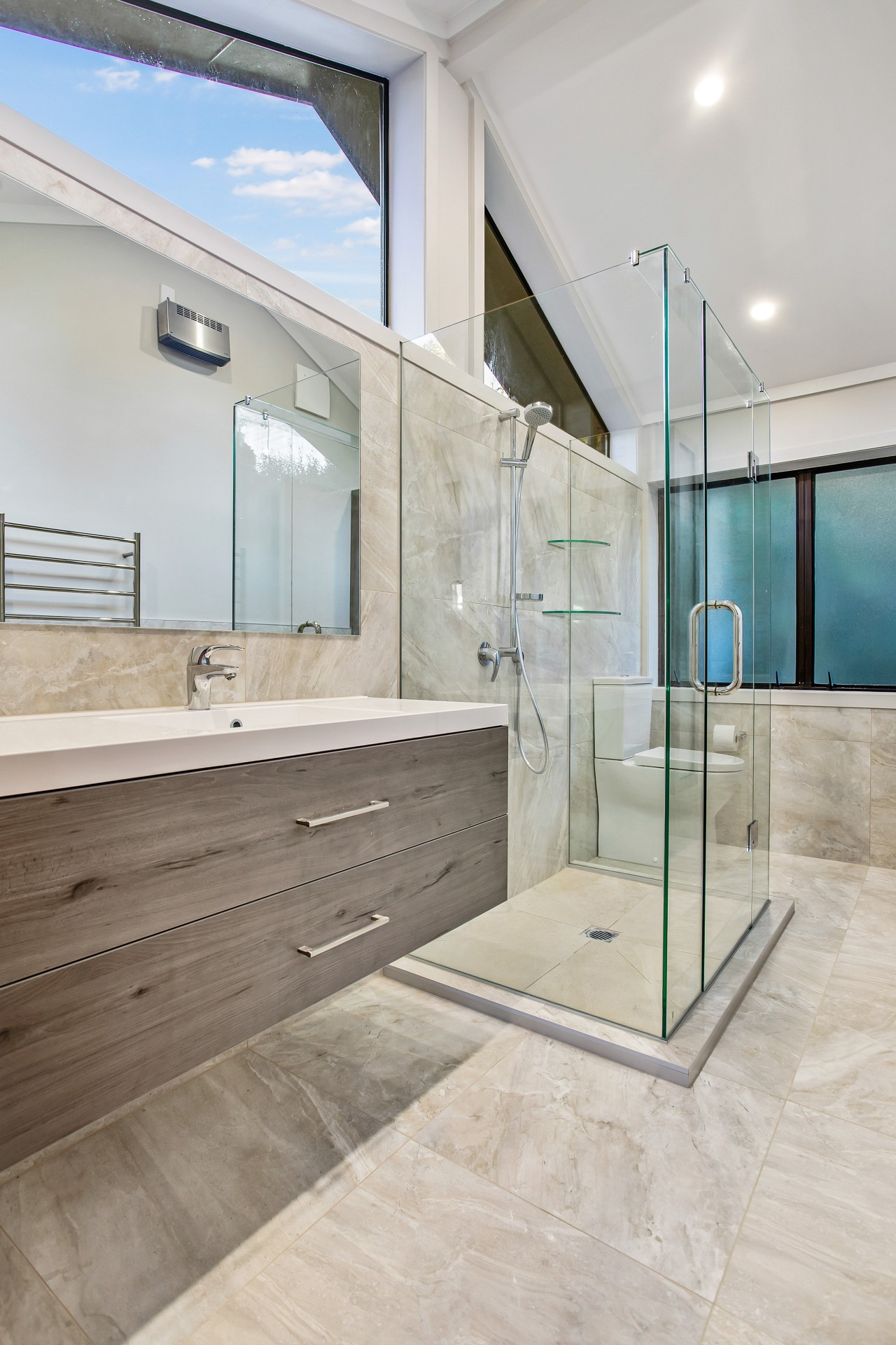 The cantilevered vanity and transparent glass shower stall apartment, architecture, bathroom, building, ceiling, daylighting, estate, floor, flooring, furniture, glass, home, house, interior design, property, real estate, room, space, tile, wall, window, gray