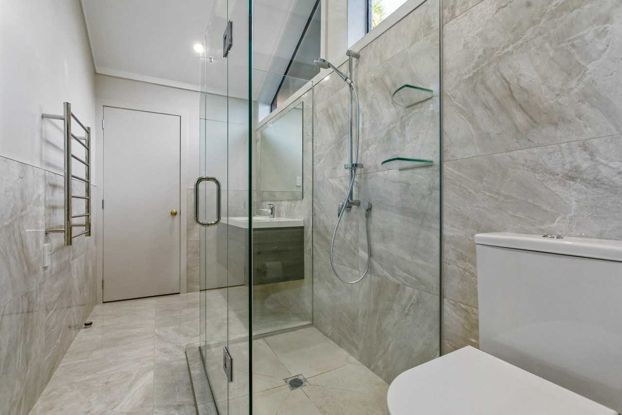 The uniform use of a stone-look tile gives architecture, bathroom, building, floor, flooring, glass, house, interior design, marble, plumbing fixture, property, real estate, room, shower, space, tile, wall, gray