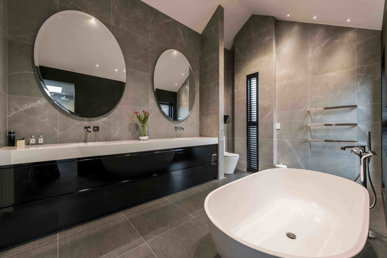 This bathroom fulfils the clients' request for a architecture, bathroom, bathroom sink, bathtub, building, ceiling, ceramic, floor, flooring, house, interior design, marble, mirror, plumbing fixture, property, real estate, restroom, room, sink, tap, tile, toilet, wall, gray, black