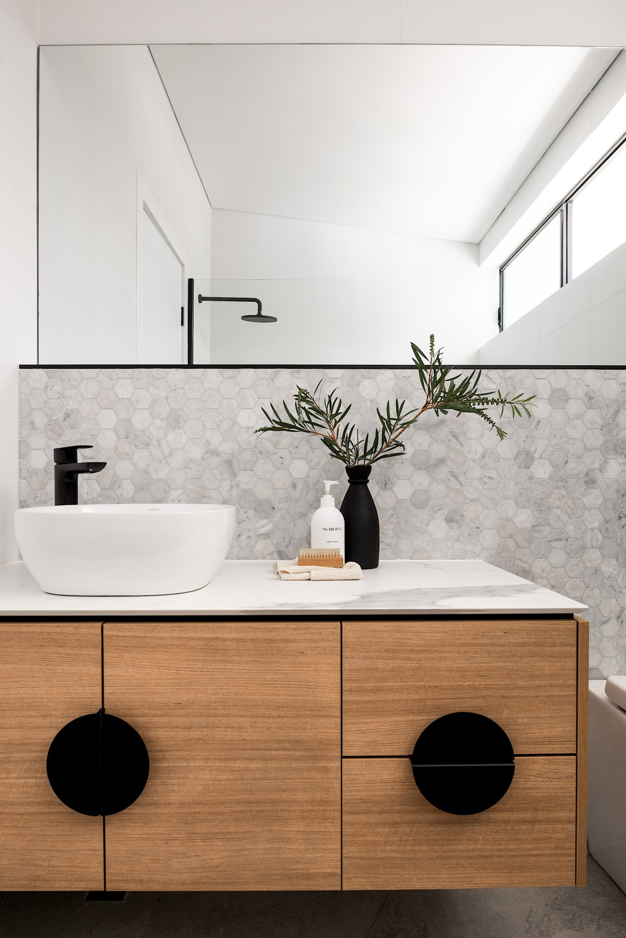A wood vanity adds warmth to the minimalist