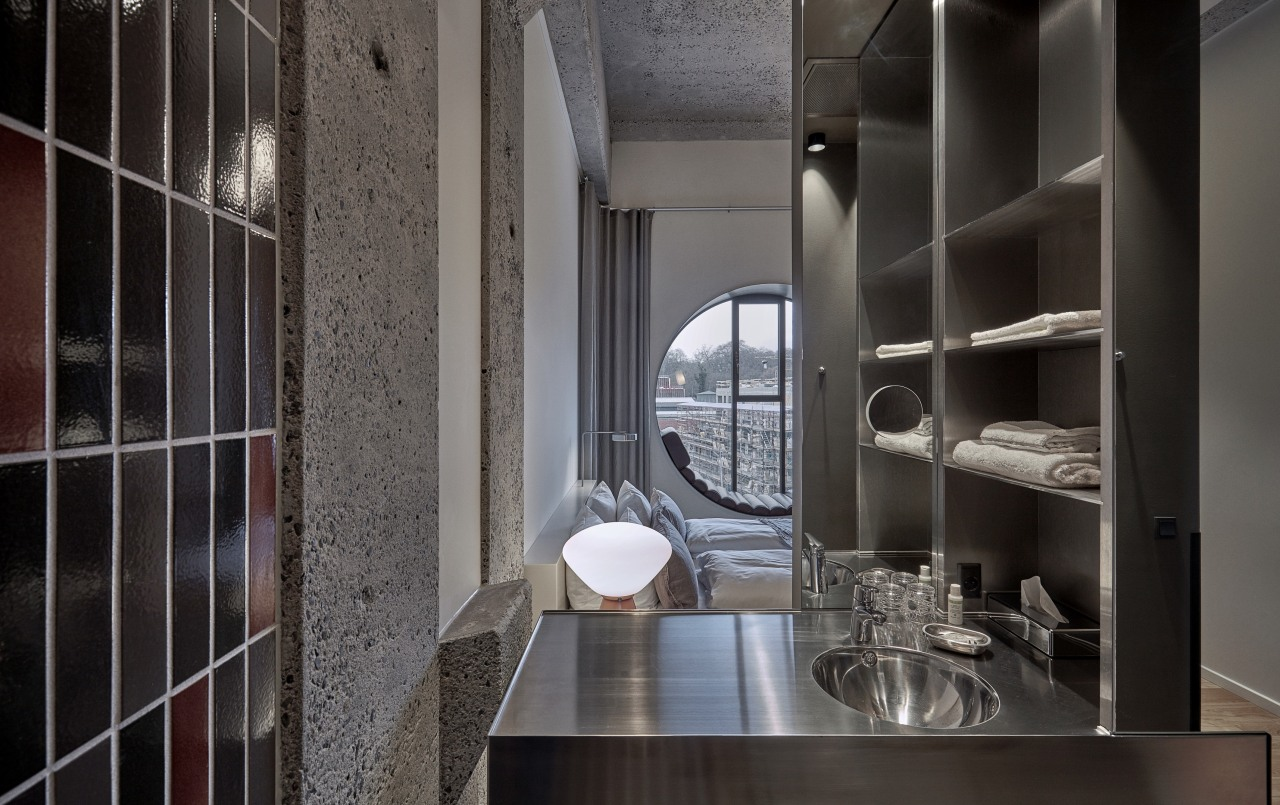 Exposed concrete surfaces contribute to the hotel's industrial-chic architecture, building, cabinetry, cupboard, furniture, house, interior design, loft, property, room, shelf, shelving, tile, black, gray