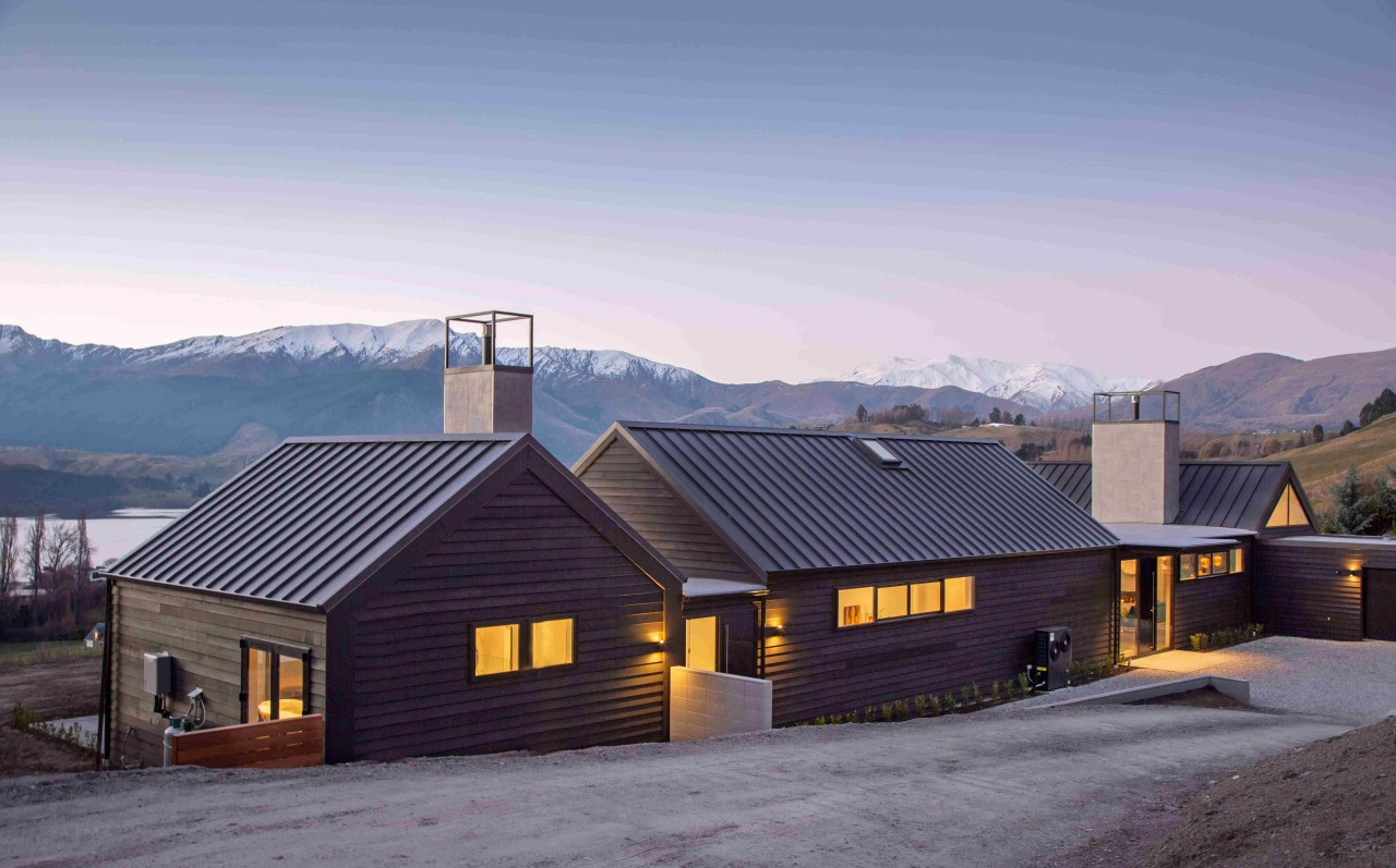 The house is wrapped in black cedar weatherboards