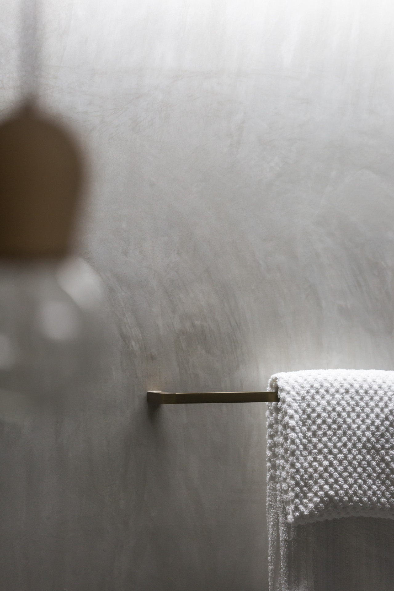 Burnished brass accessories bring a rich accent to floor, wall, grey tiles,  Arc Seven, towel rail, brass