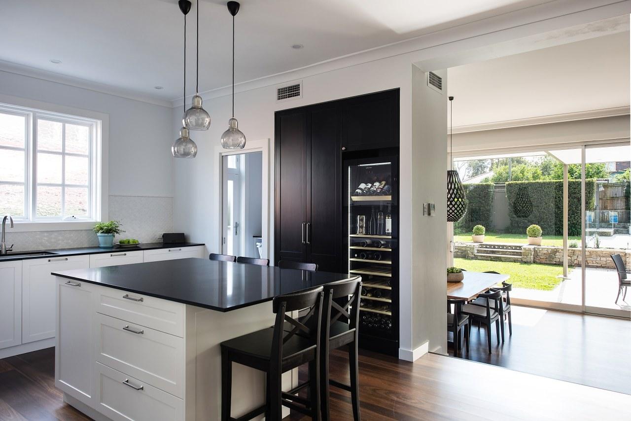 In this heart-of-the-home kitchen, the tall black pantry countertop, classique, interior design, kitchen, cabinetry, black, white, Caesarstone, wine fridge, vintec, IL Design,