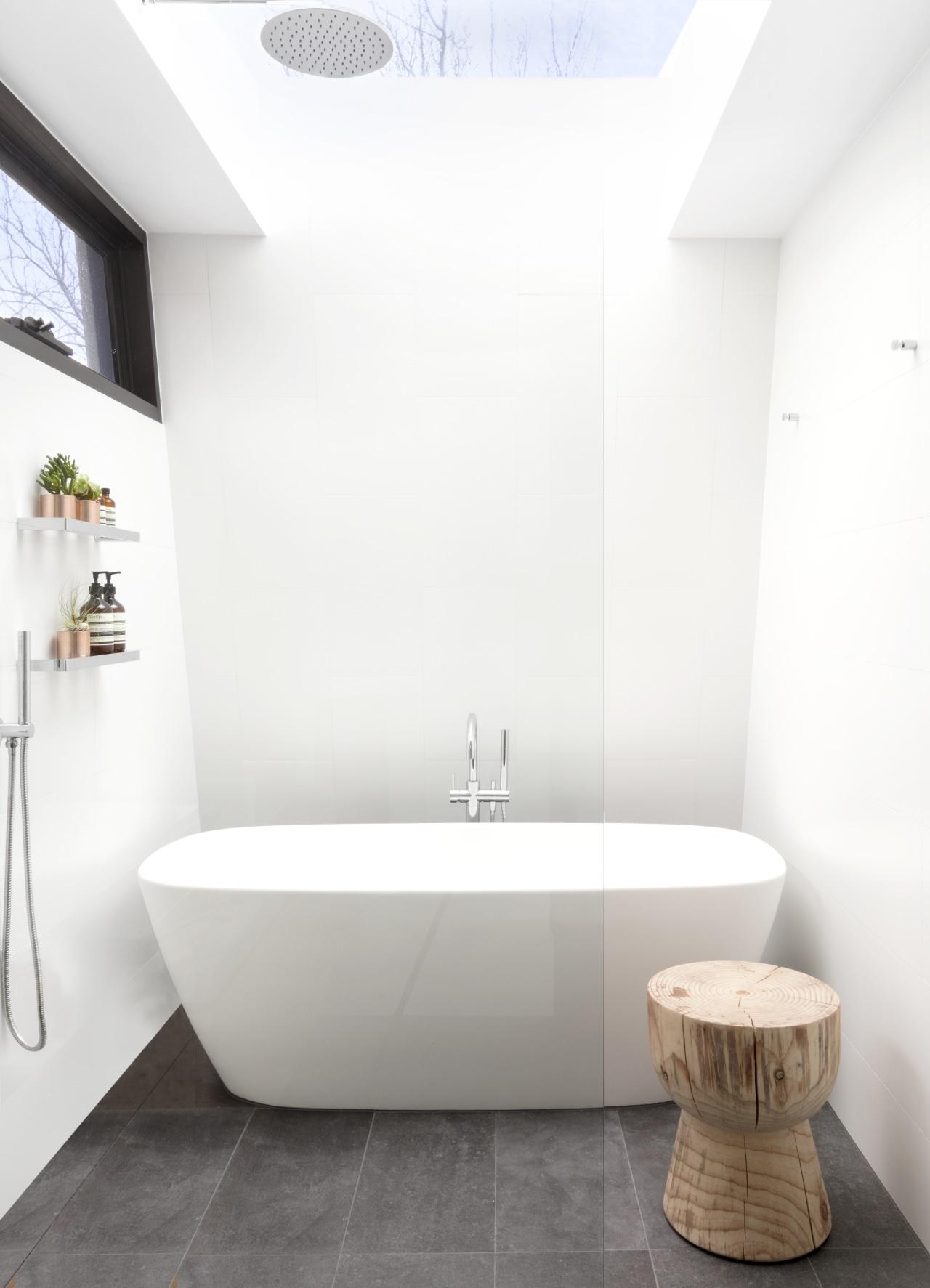 A large skylight over the shower, a soft-edged architecture, bathroom, bathtub, ceramic tiles, floor, flooring, plumbing fixtures, tap, tile, rainhead shower
