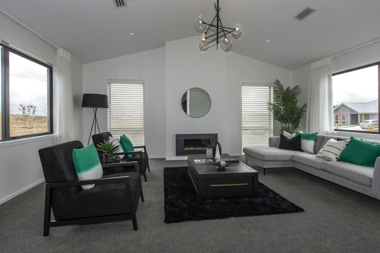 ​​​​​​​This Fowler Homes Waikato showhome is warm year-round building, ceiling, ceiling fan, coffee table, den, floor, furniture, green, hardwood, home, house, interior design, living room, mechanical fan, property, real estate, room, table, gray, black
