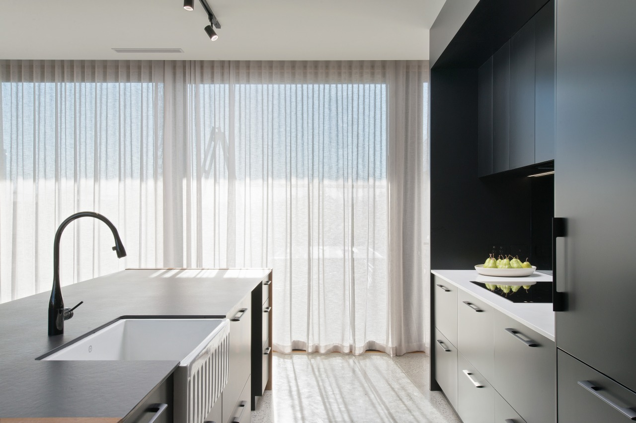 ​​​​​​​Set just below the slender Dekton island benchtop, architecture, Kitchen, countertop, benchtop, Dekton, curtain, plumbing fixture, butler sink, tap, tile, Impact Kitchens
