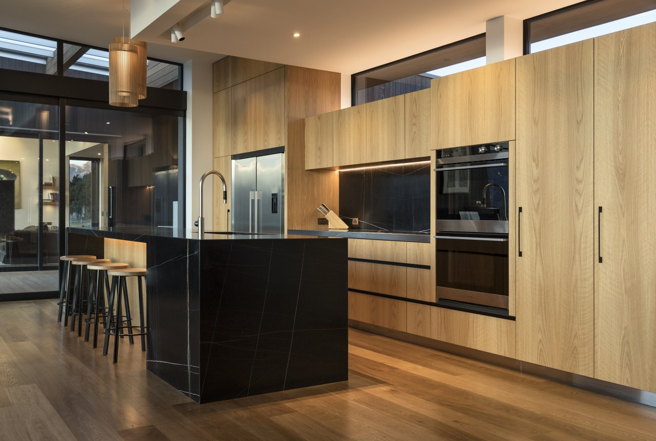​​​​​​​Recessed track spots above this benchtop provide a architecture, kitchen, cabinetry, countertop, cupboard, timber flooring, home, house, interior design, kitchen, wood flooring, wood stain, brown, black, lighting, feature lighting, fisher & Paykel, Eliska Lewis Architects