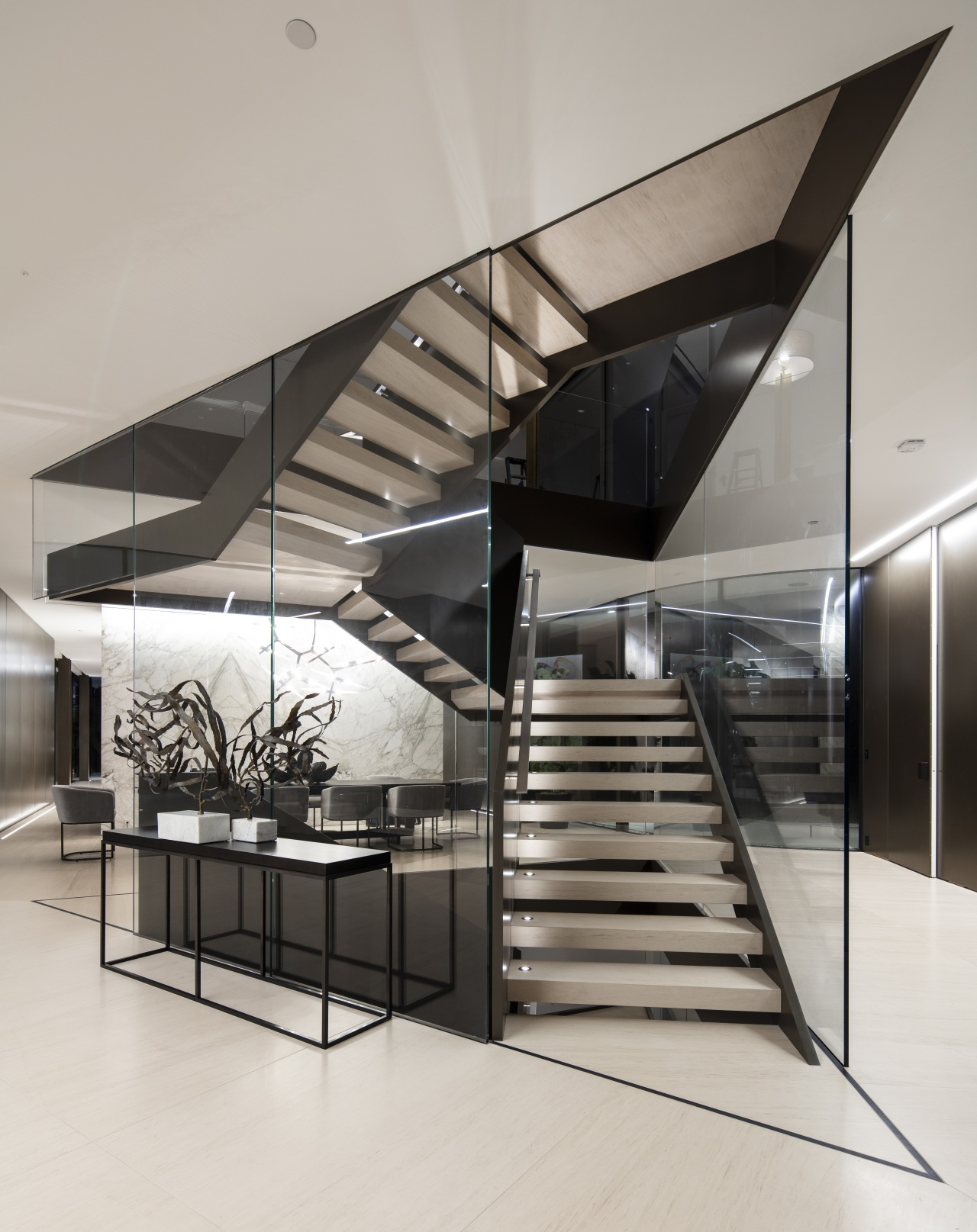 ​​​​​​​Visitors encounter a dynamic glass and steel staircase architecture, black-and-white, building, ceiling, daylighting, design, floor, limestone floor,  stair, staricase, glass, handrail, house, interior design, line, lobby, material property, metal, real estate, room, stairs, gray