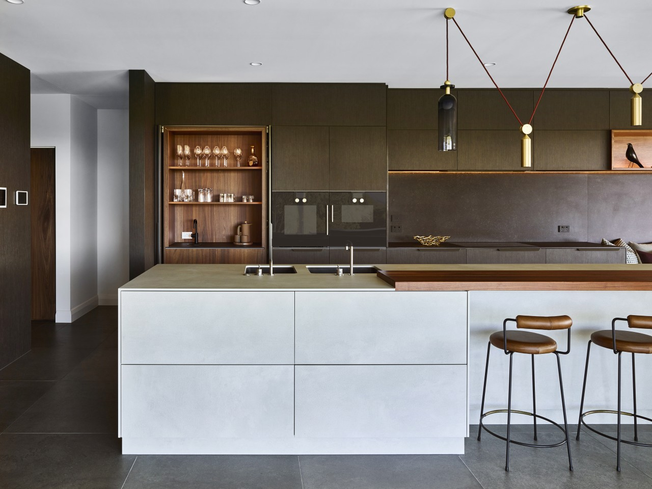 ​​​​​​​This kitchen by designer Darren James features dark architecture, bar stool, cabinetry, countertop, Darren James, wood veneer, porcelain sheeting, drinks station