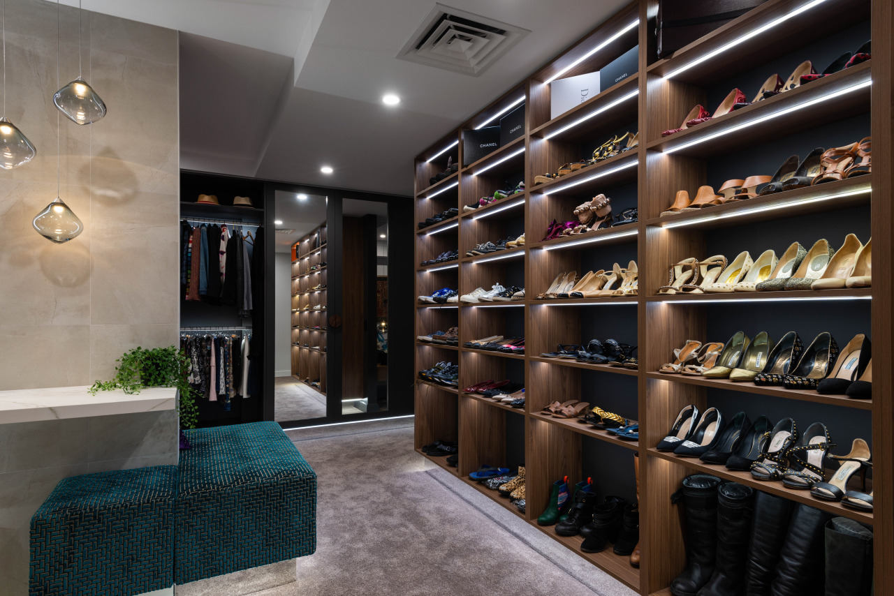 A green ottoman is positioned at the centre building, ceiling, closet, footwear, furniture, interior design, room, shelf, shelving, shoe, shoe store, wine cellar, winery, black, gray