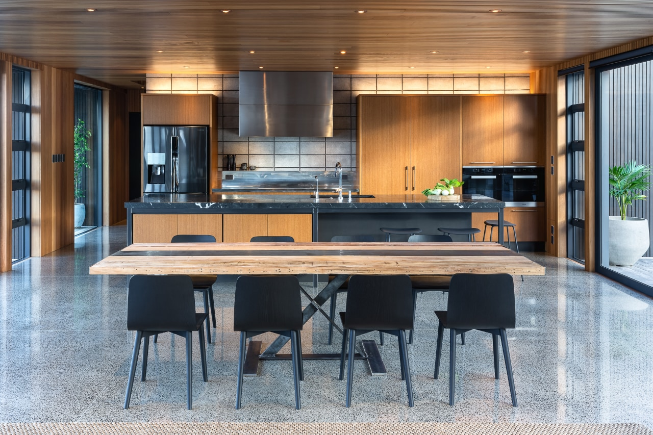 ​​​​​​​This kitchen by Kitchen Architecture presents as a architecture, bar stool, building, cabinetry, ceiling, countertop, dining room, floor, flooring, furniture, hardwood, home, house, interior design, kitchen, material property, property, real estate, room, table, wood, gray