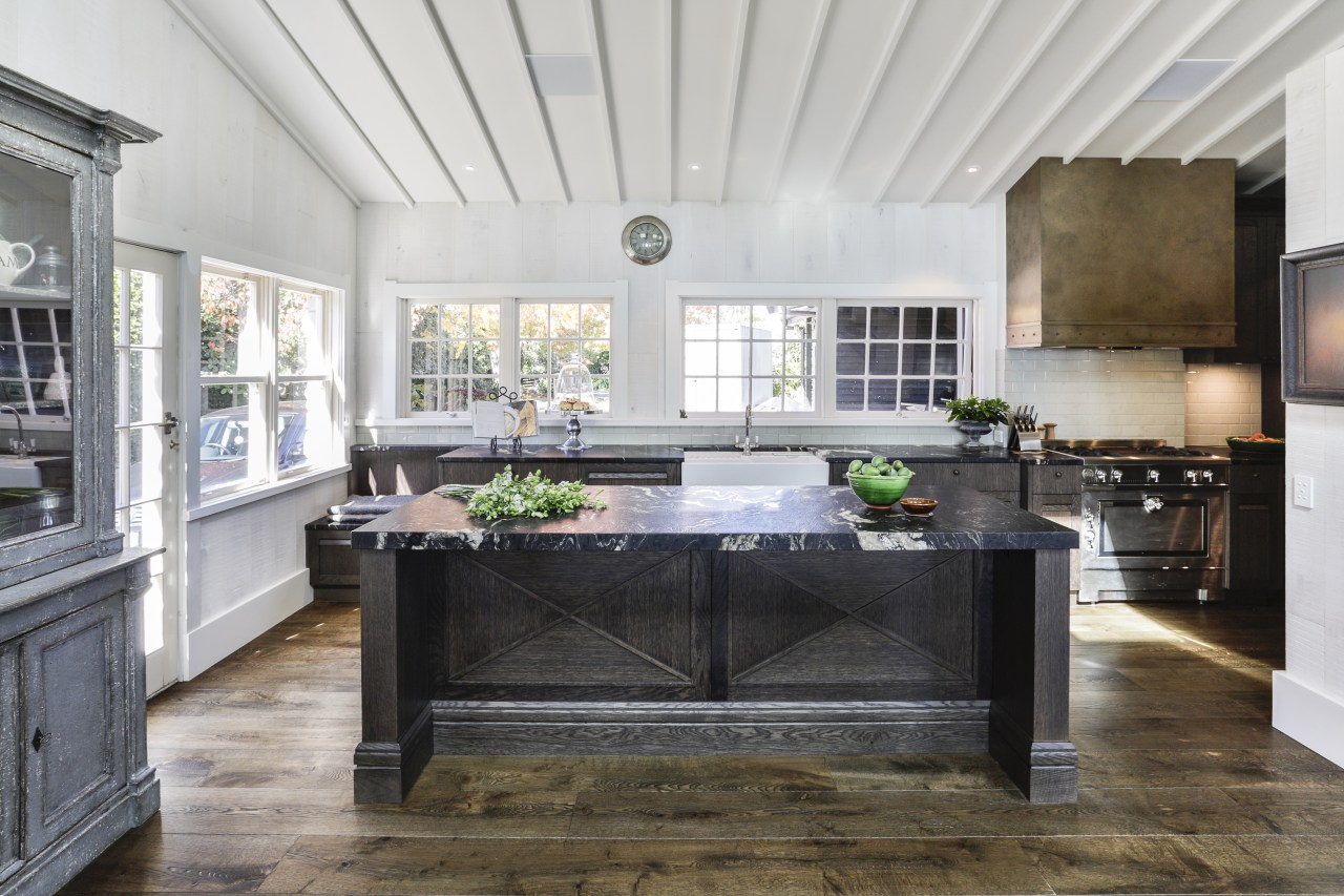 Elegant chocolate-stained oak cabinetry panelling and chunky leathered gray, white