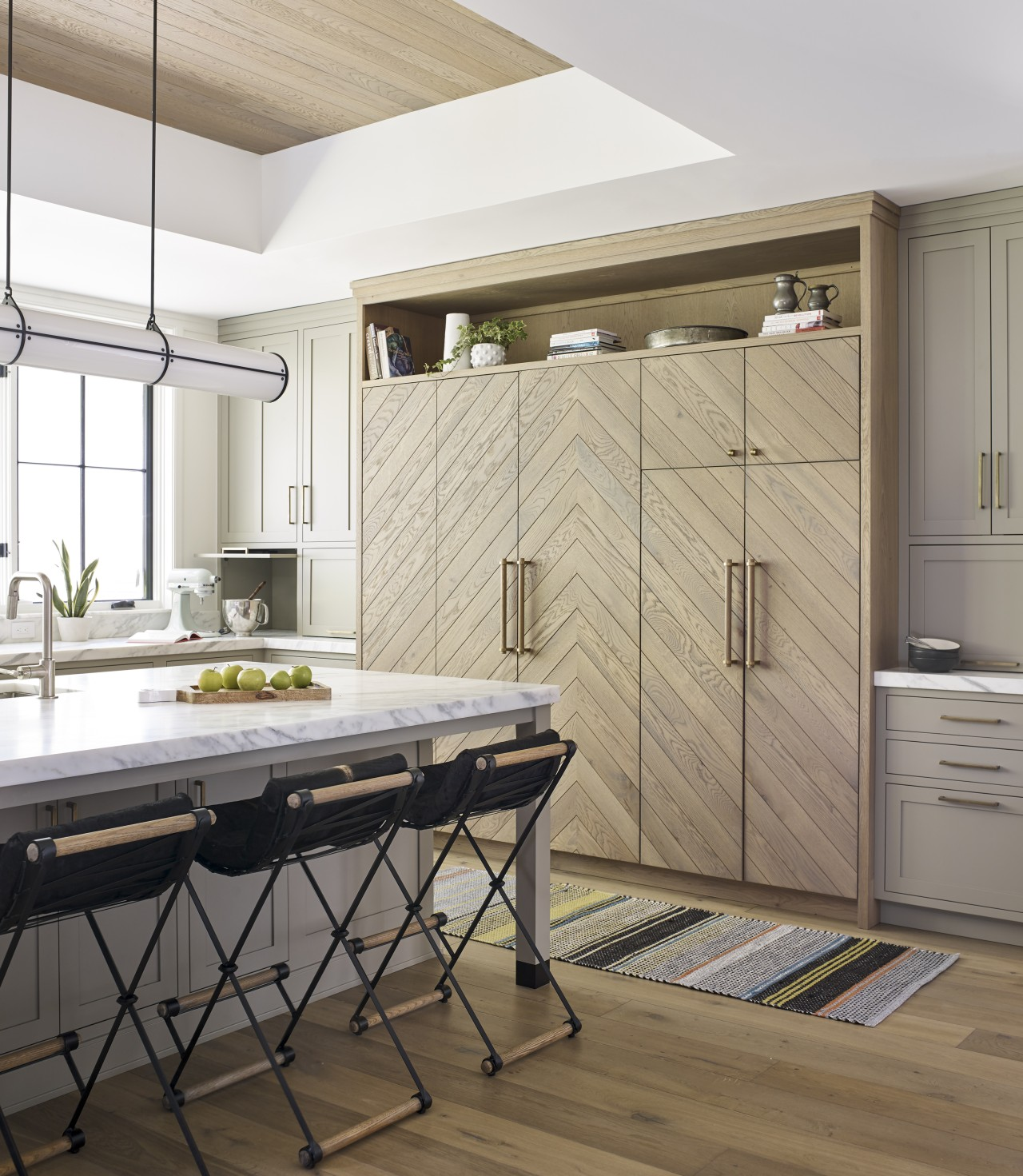 ​​​​​​​In this kitchen, classic paneled down-to-counter cabinetry hides