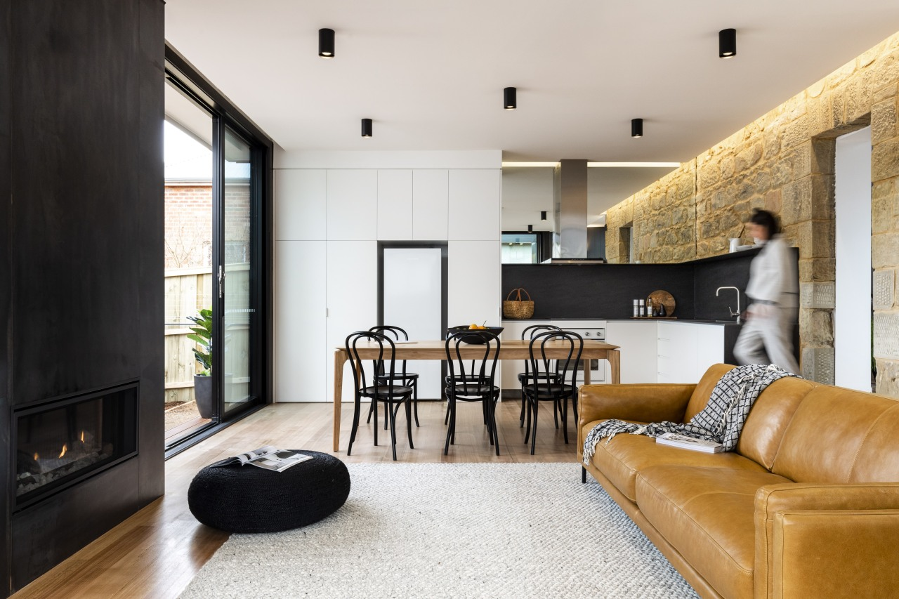 New wood floors connect tonally with original sandstone white, black