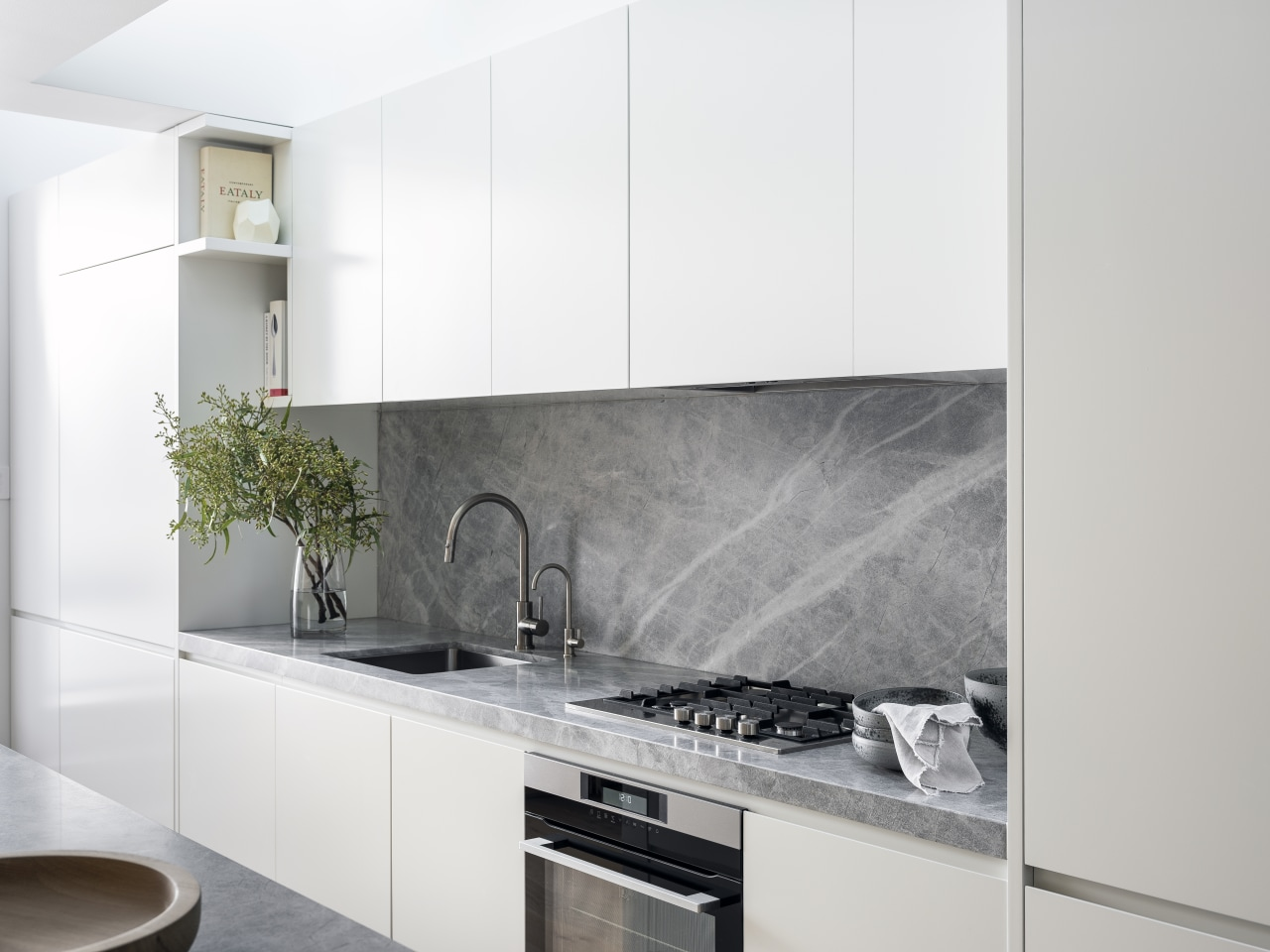 This white kitchen's benchtops and splashback are in