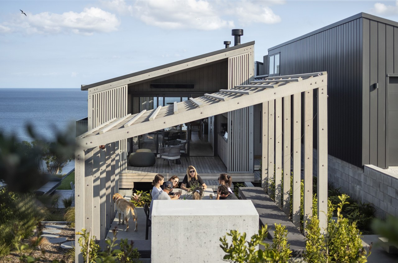 The outdoor dining space, situated under the pergola,
