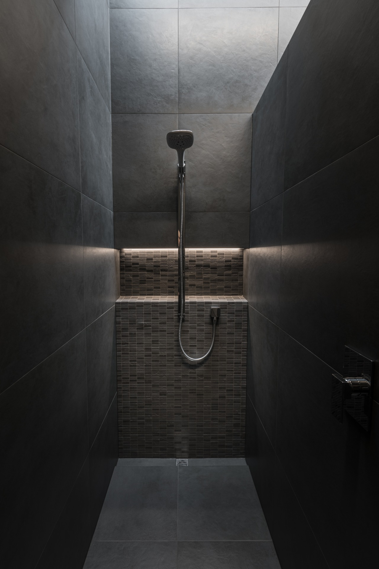 The layout incorporates a practical and private shower architecture, bathroom, black, concrete, floor, flooring, interior design, line, plumbing fixture, room, shower, tile, black